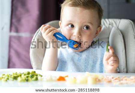 Baby boy sitting and having dinner eating - stock photo