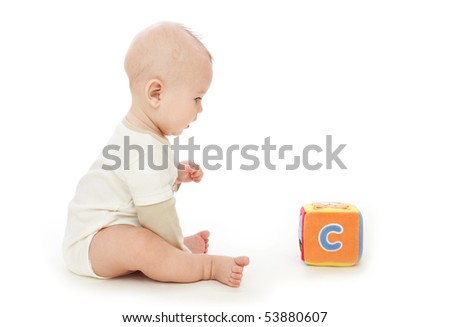 Baby boy sitting and playing with a colorful block, on white background