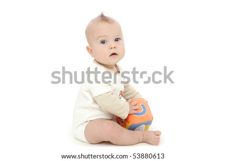 Baby boy sitting and playing with a colorful block, on white background - stock photo