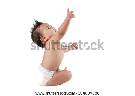 Baby boy sitting and stretch out his hand for something - stock photo
