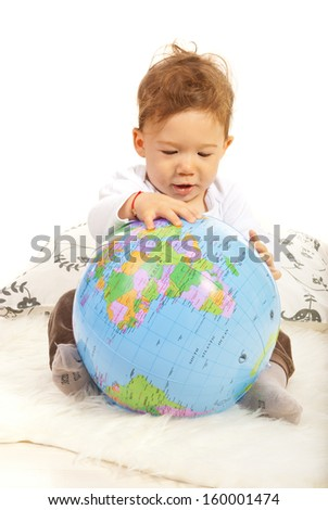 Baby boy sitting down and searching world globe - stock photo