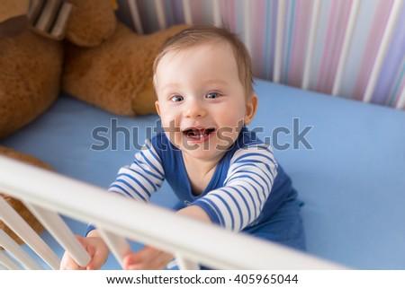 Baby boy sitting in the crib - stock photo