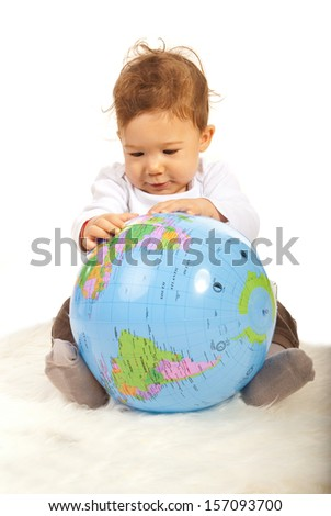 Baby boy sitting on fur blanket and searching on a world globe - stock photo