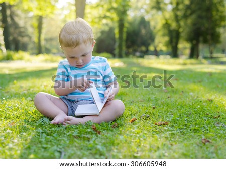 Baby boy sitting on grass in park and looking at book
