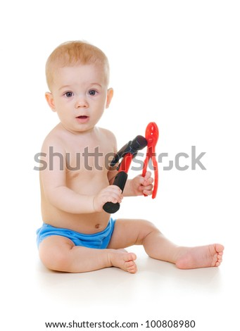 Baby boy sitting on the floor and holding tools - stock photo
