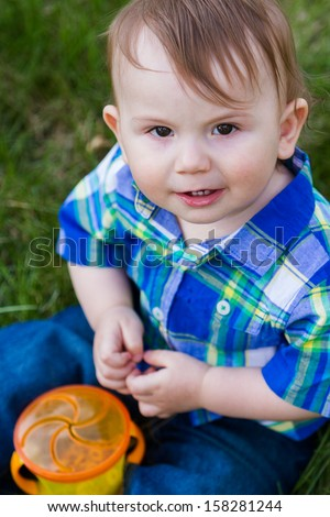 Baby boy sitting on the grass.