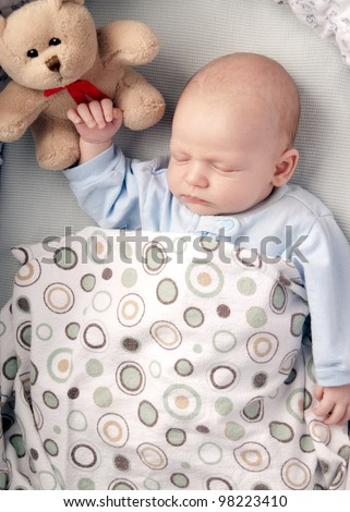 baby boy  sleeping in a basinet  with a stuffed teddy bear - stock photo