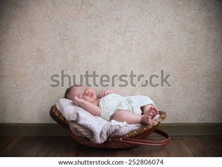 Baby boy sleeping in the basket on the wooden floor - stock photo