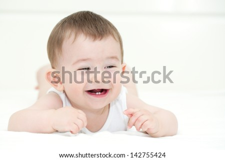 Baby boy smiling and showing his first teeth. Indoors, close up with copy space - stock photo