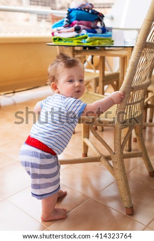 Baby boy standing at the chair on balcony - stock photo