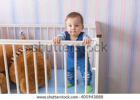 Baby boy standing for a first time at the crib - stock photo