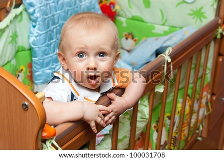 Baby boy standing in cot (crib) and looks up - stock photo