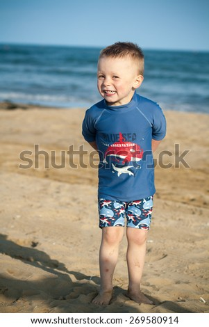 baby boy standing on the beach, looking at camera and smiling, hands are behind his back, dressed in swimming suit with UV protection - stock photo