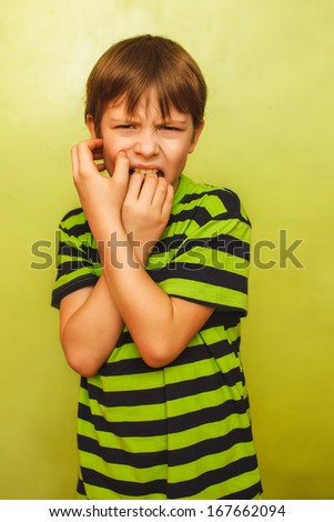 baby boy teenager feels fear anxiety anxiety bad habit of biting your nails on a green background expression of emotions - stock photo