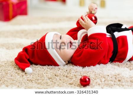 Baby boy weared Santa costume hollding christmas ball - stock photo