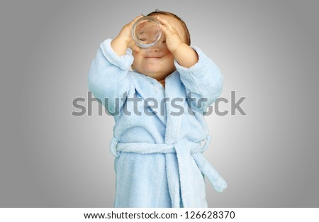 Baby boy wearing a bathrobe and holding a glass against a grey background - stock photo