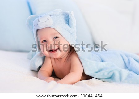 Baby boy wearing diaper and blue towel in white sunny bedroom. Newborn child relaxing in bed after bath or shower. Nursery for children. Textile and bedding for kids. New born kid with toy bear. - stock photo
