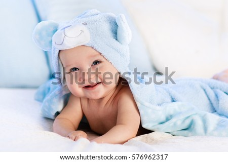 Baby boy wearing diaper and blue towel in white sunny bedroom. Newborn child relaxing in bed after bath or shower. Nursery for children. Textile and bedding for kids. New born kid with toy bear
