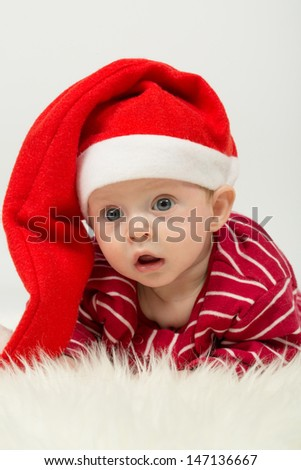 Baby boy with big eyes and with his mouth open in Santa Claus cap