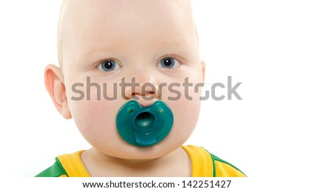 Baby boy with blond hair and yellow shirt with blue pacifier on white background