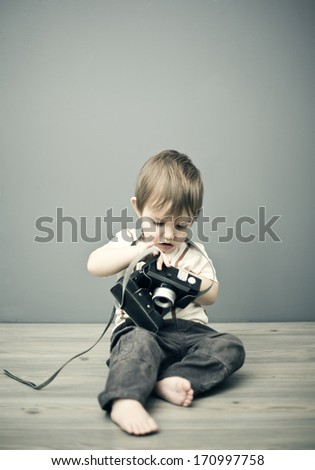 Baby boy with camera  - stock photo
