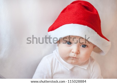 Baby boy with Christmas cap and balls on white background