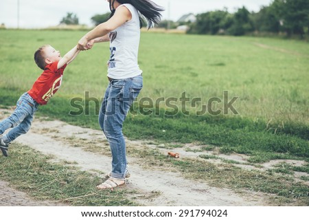 baby boy with her mom walk on the field road - stock photo