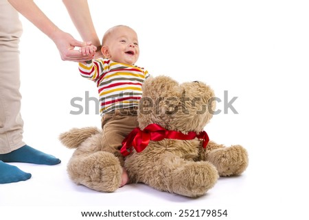 Baby boy with his mother plays on plush dog on white background - stock photo