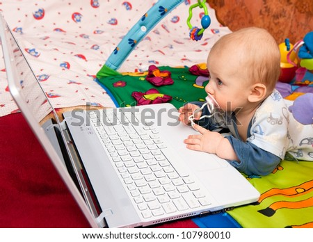 Baby boy with interest works with (computer) laptop - stock photo