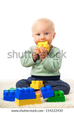 Baby boy with playing with construction set  - stock photo