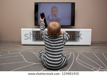 baby boy with remote controls watching television - stock photo