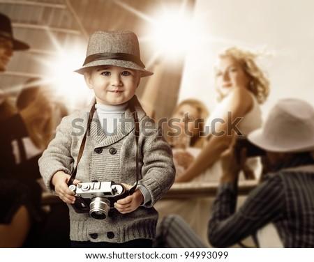 Baby boy with retro camera over photo shoot background. - stock photo