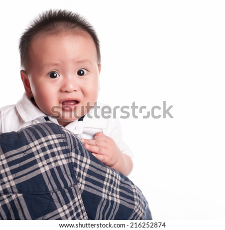 Baby boy with sad expression. Baby scared. Holding his father. Looking at camera. - stock photo