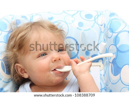 Baby boy with spoon smiling.