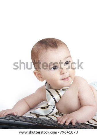 Baby boy with tie typing on computer keyboard - stock photo