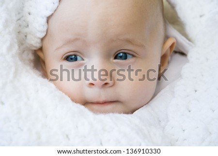 baby boy wrapped in a white blanket in the outdoors - stock photo
