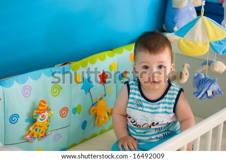 Baby boy ( 1 year old ) sitting in baby bed at children's room, looking up. - stock photo