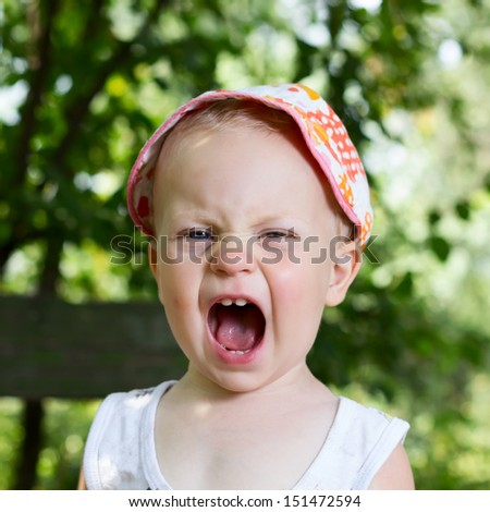 Baby boy (1 year) screaming on nature background. - stock photo