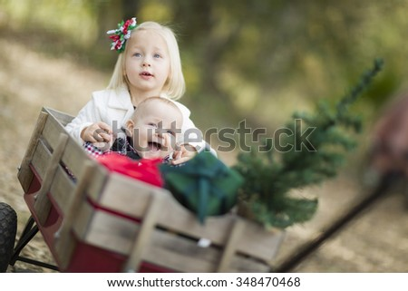 Baby Brother and Sister Being Pulled in Wagon with Christmas Tree and Gifts Outdoors. - stock photo