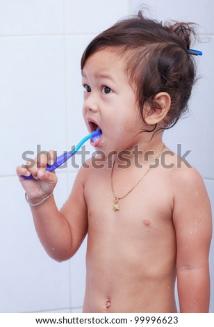 Baby brushes his mouth with toothbrush