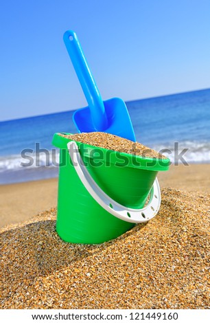 Baby bucket with sand and a shovel on the beach against the azure sea - stock photo