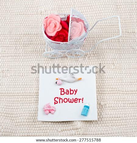 Baby card - baby shower theme. Pram full of flowers on white textile background. Newborn greeting card. - stock photo