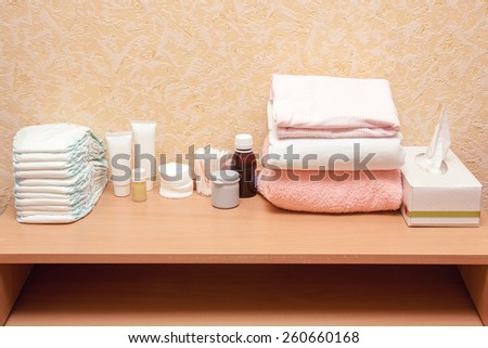 Baby care essentials on the diaper table: diapers, cream, napkins, bottles, oil, cloth and towel  - stock photo