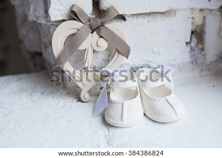 baby ceramic shoes and a heart - stock photo