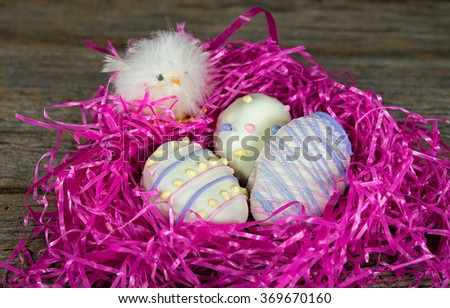 baby chick with Easter egg cookies in pink grass nest on rustic wood - stock photo
