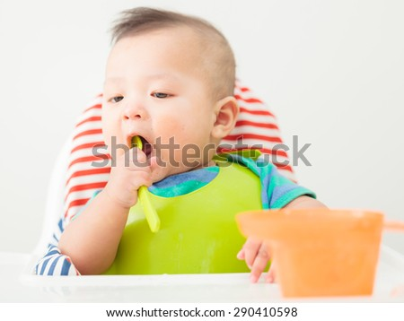 baby child eating in chair - stock photo