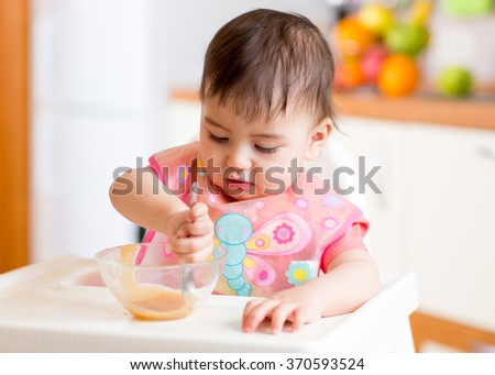 baby child sitting in chair with a spoon and eating healthy food