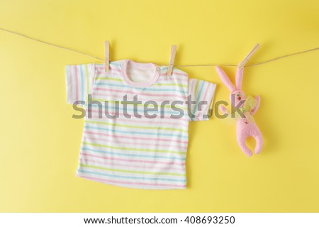 Baby clothes and easter rabbit on a clothesline - stock photo