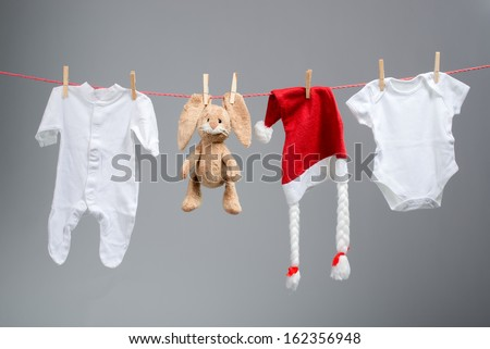 Baby clothes and santa hat on a clothesline - stock photo