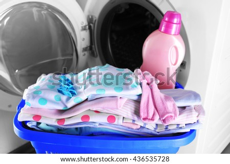 Baby clothes and washing machine, close up - stock photo